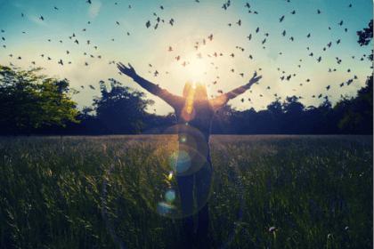 Donna felice con le braccia sollevate e uccelli che volano.