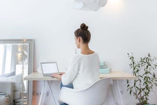 Donna lavora in un ambiente con mobili bianchi.