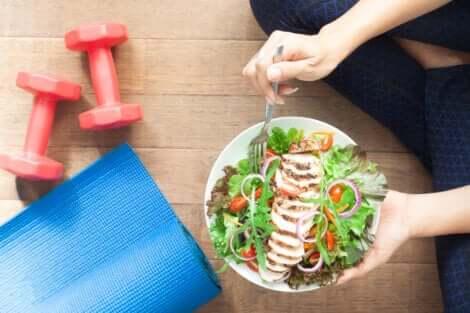 Donna con piatto di insalata e attrezzi per la palestra.
