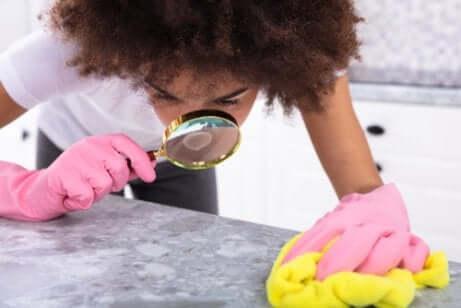 Donna pulisce con guanti e lente di ingrandimento.
