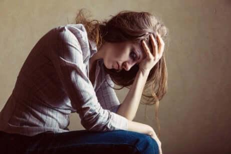 Donna seduta con atteggiamento depresso.