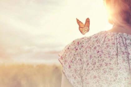 Farfalla sulla spalla di una donna.