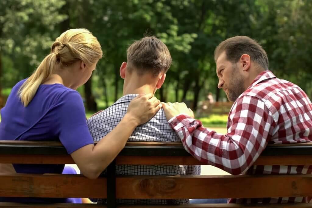 Genitori che parlano col figlio adolescente.