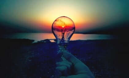 Mano con lampadina e tramonto.