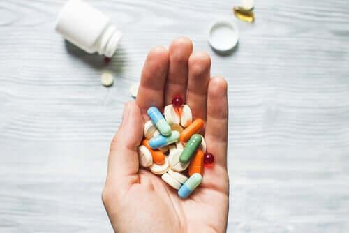 Mano piena di pasticche di medicinali.