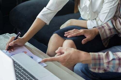 Uomo che poggia una mano sulla gamba della donna.