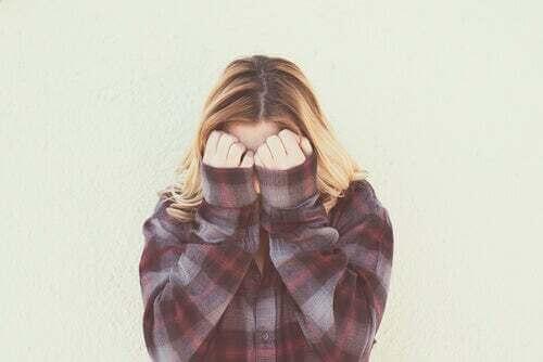 Ragazza che si copre il viso con le mani.