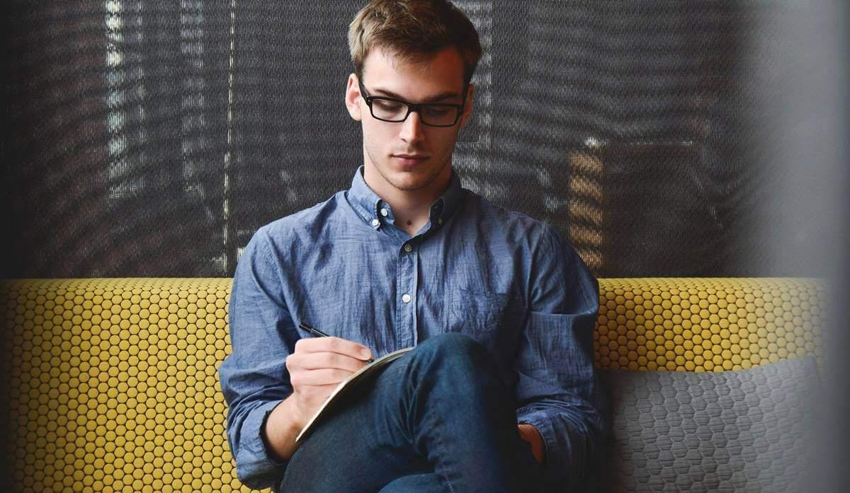 Ragazzo con occhiali che scrive.