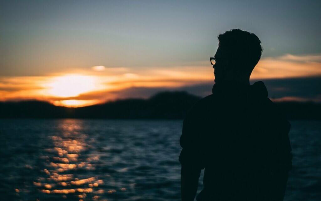 Ragazzo con occhiali davanti al mare.