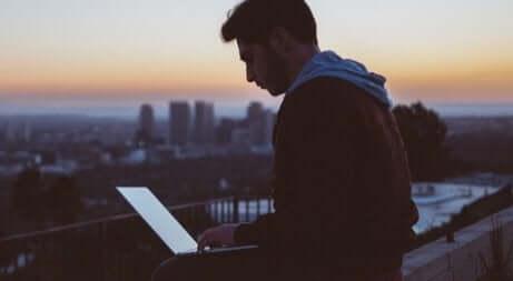 Ragazzo lavora al computer di fronte a panorama urbano.