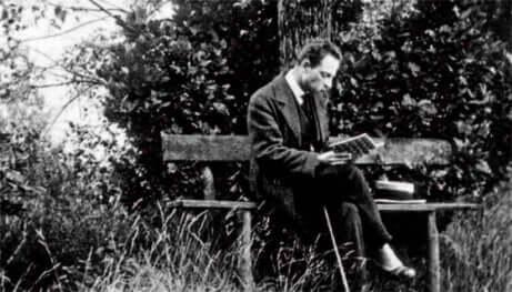 Reiner Maria Rilke legge seduto sulla panchina.