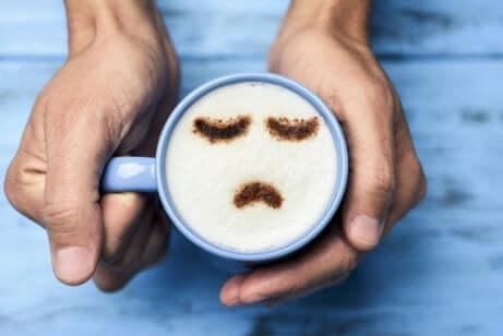 La origine della infelicità e tazza con faccina triste.