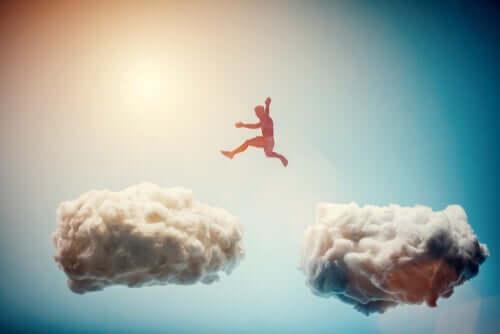 Uomo che salta tra le nuvole.