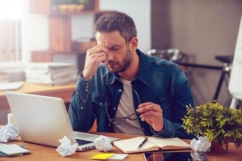 Uomo con mal di testa causa lavoro.