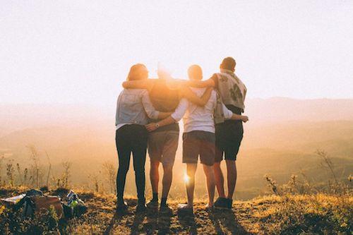 Amici che si abbracciano guardando il sole da una collina.