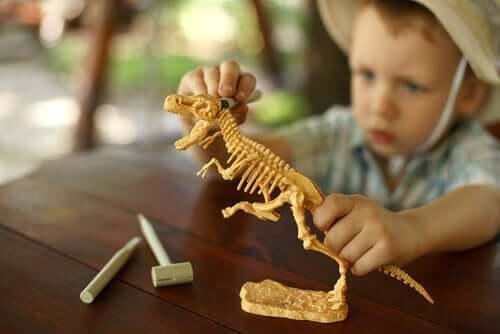 Bambino gioca con modellino di dinosauro.