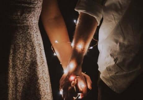 Coppia con mani legate insieme da un filo luminoso.