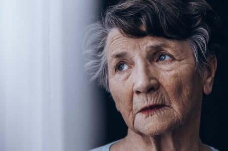 Donna anziana con sguardo assente e morbo di Alzheimer.