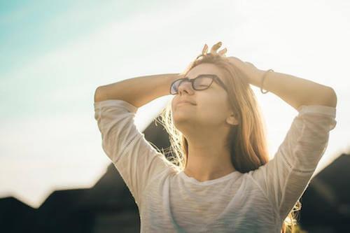 Donna che respira profondamente in una bella giornata di sole.