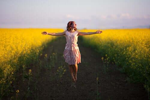 Donna felice in mezzo a un sentiero tra i fiori.