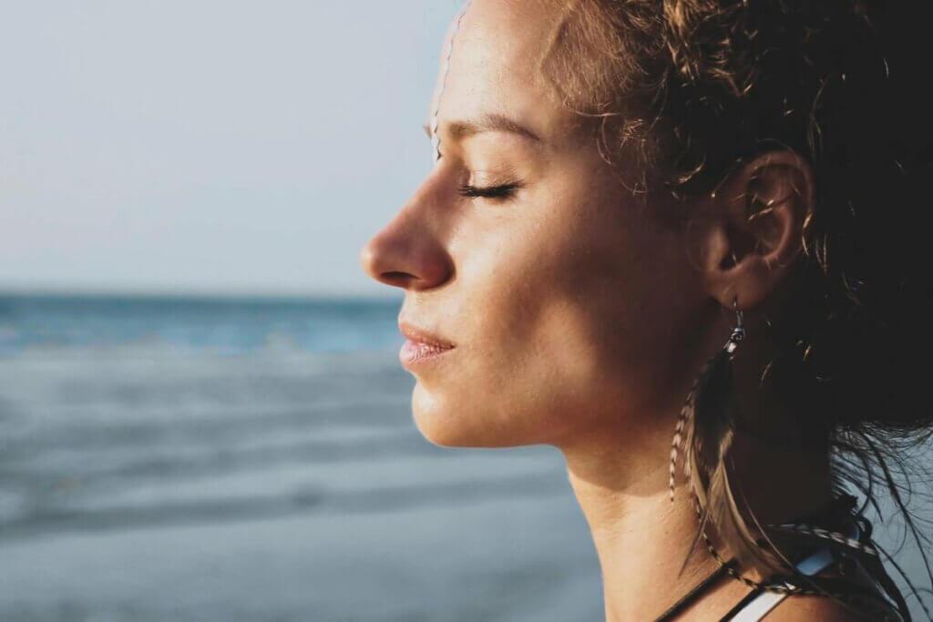 Donna con gli occhi chiusi vicina al mare