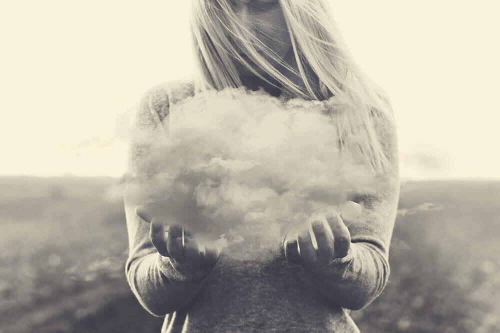 Donna sorregge nube che rappresenta i suoi pensieri negativi.