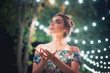 Donna sotto alberi con lucine.