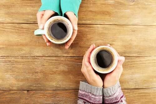Mani con tazze di caffè.