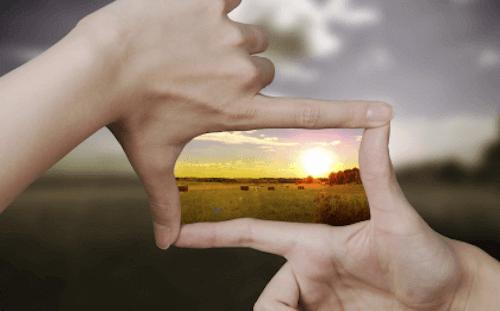 Mani posizionate a forma di inquadratura che inquadrano il sole al tramonto.