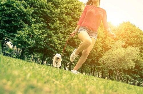 Ragazza che fa la passeggiata con il cane.