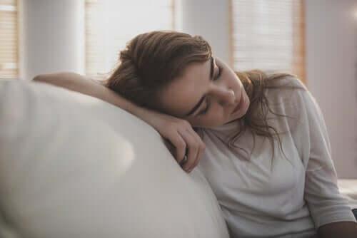 Ragazza depressa con la testa appoggiata sul divano.