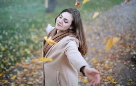Ragazza felice circondata di foglie.