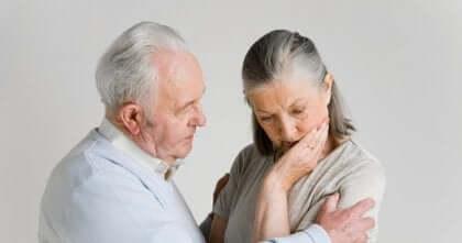 Uomo anziano parla alla moglie che è affetta da demenza.