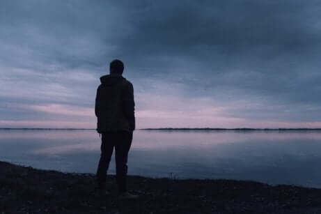 Uomo di spalle davanti al mare con depressione esistenziale.