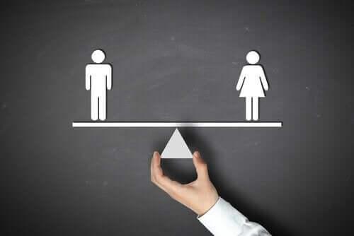 Uomo e donna su una bilancia in equilibrio e la teoria dello schema di genere.