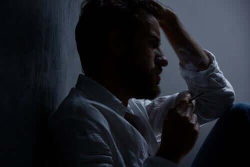 Uomo pensieroso e depresso che fuma una sigaretta. Rete neurale di default.