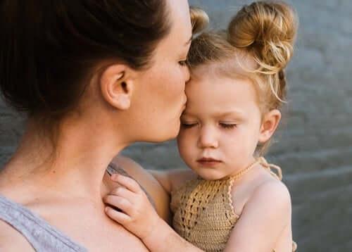 Mamma che bacia la figlia in fronte.