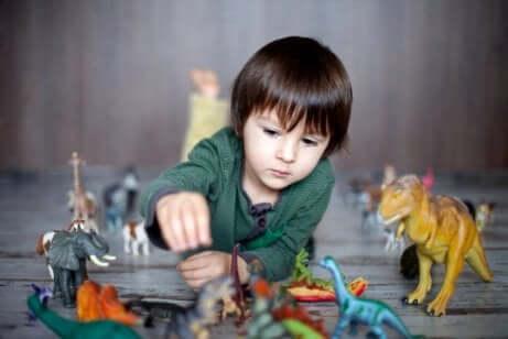 Bambino che gioca con i dinosauri.