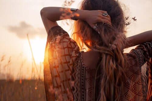 Donna con le braccia dietro la testa mentre osserva il tramonto.