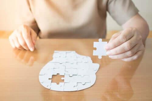 Donna che fa un puzzle che raffigura le testa di un uomo.