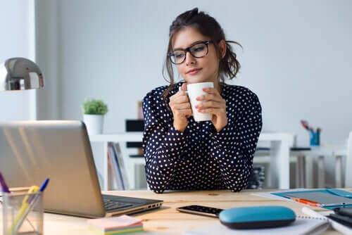 Donna con gli occhiali lavora sul portatile.