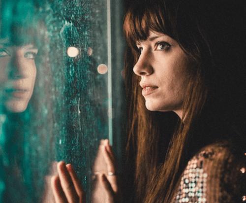 Donna che guarda fuori dalla finestra mentre piove.