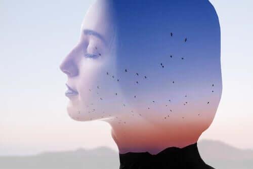 Donna trasparente con gli occhi chiusi e sullo sfondo degli uccelli in volo.