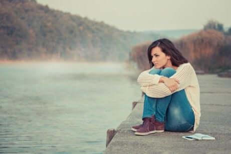 Ragazza seduta sulla sponda del fiume.