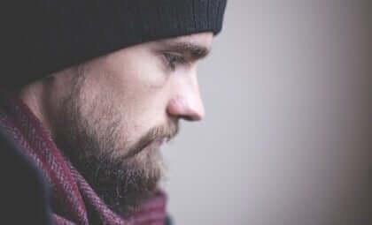 Ragazzo con barba e sguardo triste.