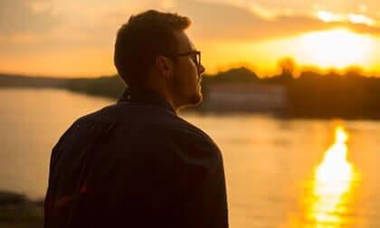 Ragazzo che osserva il tramonto sul fiume.