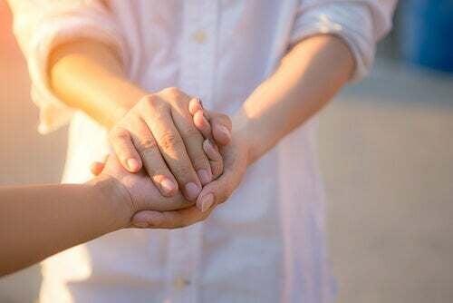Mani di una persona che tengono le mani di un'altra.