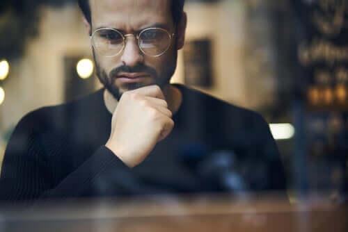 Uomo con gli occhiali pensieroso.