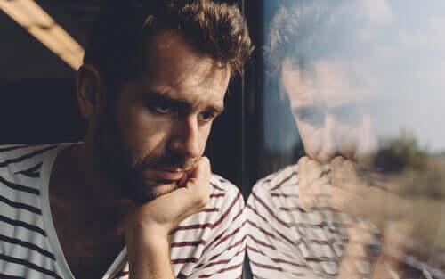 Uomo preoccupato della morte mentre guarda dalla finestra.