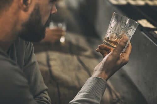 Persona che guarda bicchiere con liquore.